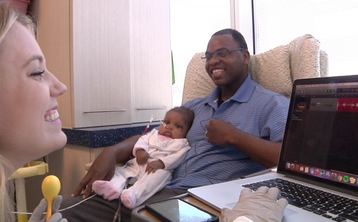 In this Friday, June 17, 2016, image from video, Bridget Sova, music therapist at Helen DeVos Children's Hospital in Grand Rapids, Mich., records the heartbeat of Julius Jackson while he holds his daughter, Mistha. Sova records the heartbeats of young patients–and sometimes their parents–and sets the sounds to music as a memory-making gift for parents and other loved ones. (AP Photo/Mike Householder)