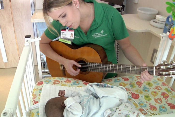 In this Friday, June 17, 2016, image made from video, Bridget Sova, music therapist at the Helen DeVos Children's Hospital, sings to Aubrey Spearman inside the infant's room at the hospital in Grand Rapids, Mich. Sova records the heartbeats of young patients and sets the sounds to music as a memory-making gift for parents and other loved ones. (AP Photo/Mike Householder)