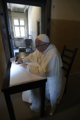 Pope Francis writes on the guest book at the end of his visit in the Nazi German death camp of Auschwitz in Oswiecim, Poland, Friday, July 29, 2016. Pope Francis paid a somber visit to the Nazi German death camp of Auschwitz-Birkenau Friday, becoming the third consecutive pontiff to make the pilgrimage to the place where Adolf Hitler's forces killed more than 1 million people, most of them Jews. (L'Osservatore Romano /Pool Photo via AP)