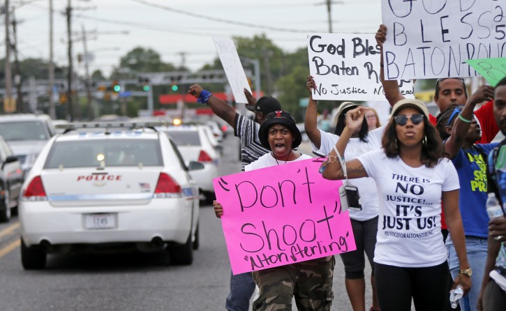People demonstrate in the street as police cars pass outside the Triple S convenience store during a rally after Alton Sterling, a black man, was shot and killed Tuesday, in Baton Rouge, La., Wednesday, July 6, 2016. The U.S. Justice Department opened a civil rights investigation Wednesday into the video-recorded police killing of Sterling, who authorities say had a gun as he wrestled with two white officers on the pavement outside a convenience store. (AP Photo/Gerald Herbert)