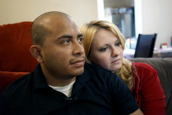 Dallas Police Department Officer Jorge Barrientos, left, is pictured recovering at his home with his girlfriend, Bethany Knutson, on Sunday, July 10, 2016, in Dallas. Barrientos was shot in the hand and struck by shrapnel when a gunman attacked officers at a protest against police brutality July 7, 2016. He recounted desperately trying to help fellow officers who were shot, including three from his unit who died. (AP Photo/Christine Armario)
