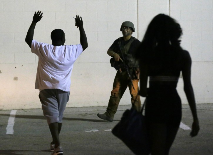 A man raises his hands as he walks near a law enforcement officer, following the shootings Thursday of several police officers in downtown Dallas, early Friday, July 8, 2016. (AP Photo/LM Otero)