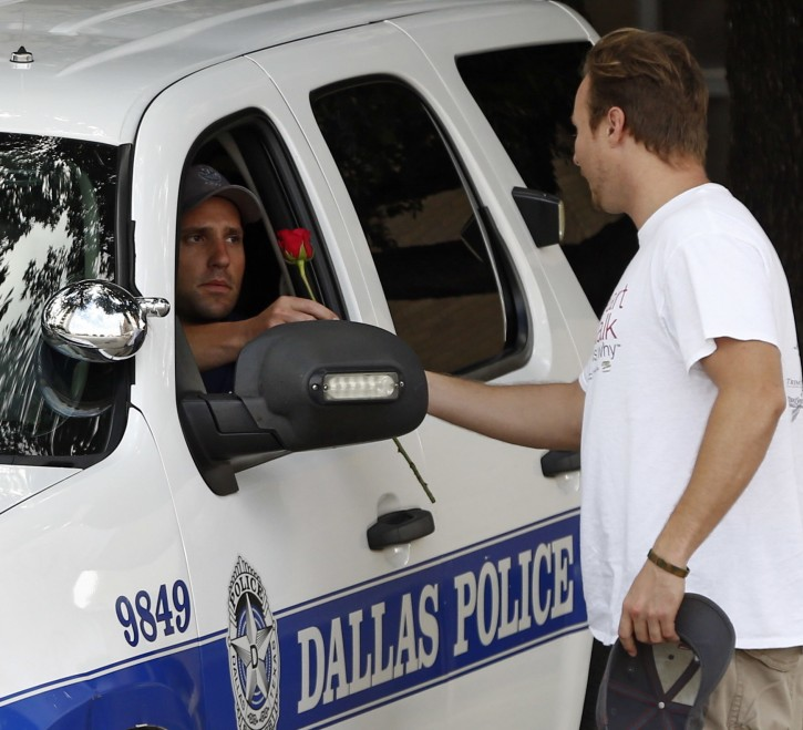 John Fife, minister at One Souls Night, hands a police officer guarding Jack Evans Police Headquarters a rose in Dallas, TX on Friday July 8, 2016 after a deadly shooting in downtown Dallas where 5 police officers were killed on the night before. (Nathan Hunsinger/The Dallas Morning News)