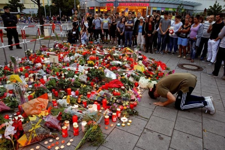 A man prays beside flowers laid in front of the Olympia shopping mall, where yesterday's shooting rampage started, in Munich, Germany July 23, 2016. REUTERS/Arnd Wiegmann