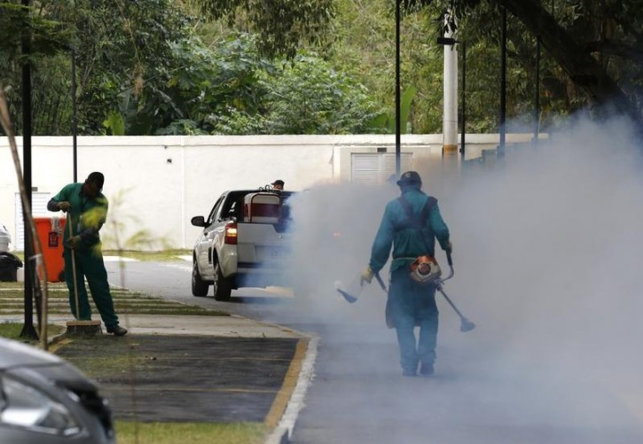 A truck sprays insecticide near grounds workers at Olympic media accomodations as part of preventive measures against the Zika virus and other mosquito-borne diseases, in Rio de Janeiro, Brazil August 29, 2016. REUTERS/Chris Helgren