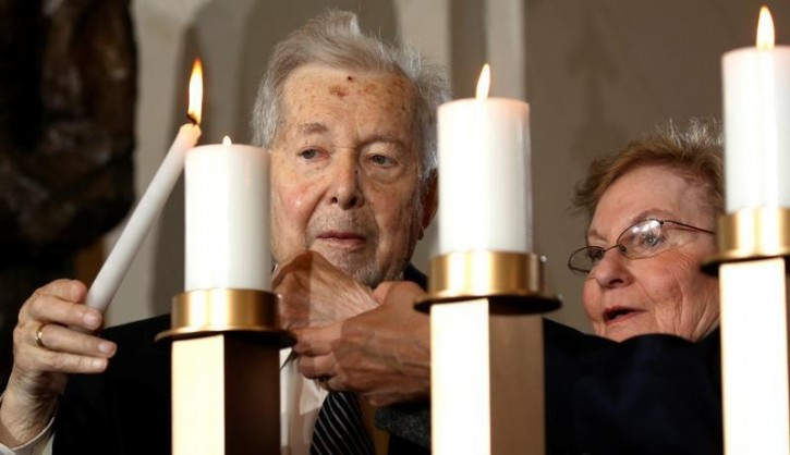 FILE - Holocaust survivors Alfred and Josiane Traum light a candle during the National Commemoration of the Days of Remembrance ceremony at the U.S. Capitol in Washington May 5, 2016. REUTERS/Kevin Lamarque