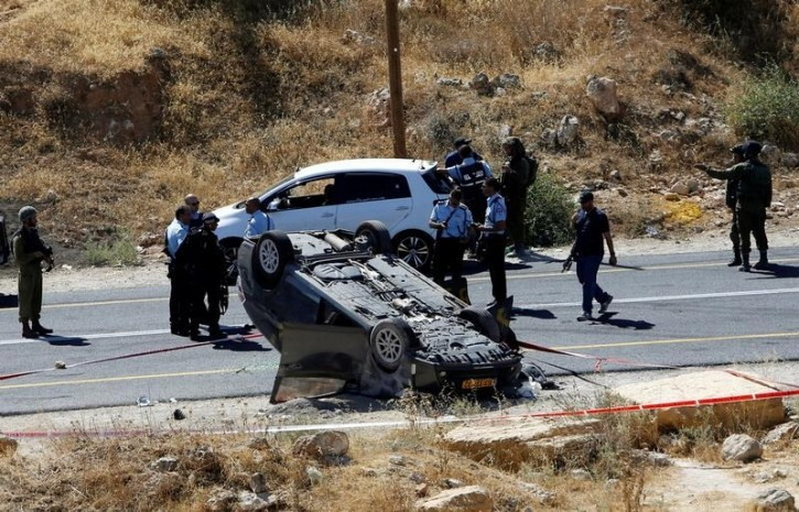 Israeli security forces gather at the scene following a shooting on an Israeli car near the West Bank city of Hebron July 1, 2016. REUTERS/Mussa Qawasma