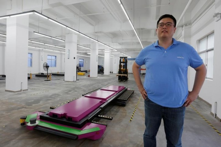 """Marco Wu, CEO of Shenzhen Yeefung Automation Technology Co Ltd, poses with a laser-guided """"parking robot"""", at a research and development centre in Shenzhen, China June 29, 2016. Picture taken June 29, 2016.   REUTERS/Bobby Yip"""
