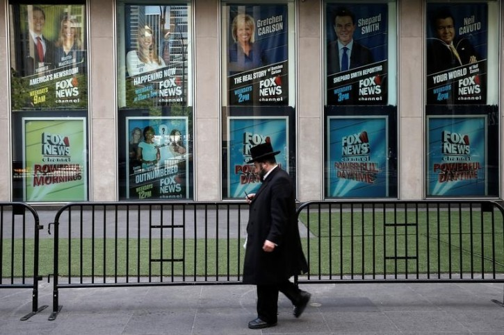 A man walks past posters of Fox News personalities including Gretchen Carlson, (C-top) who was recently fired from Fox News and who has filed a  lawsuit against Fox News Chairman and CEO Roger Ailes, at the News Corporation headquarters building in Manhattan, New York, U.S., July 6, 2016. REUTERS/Mike Segar