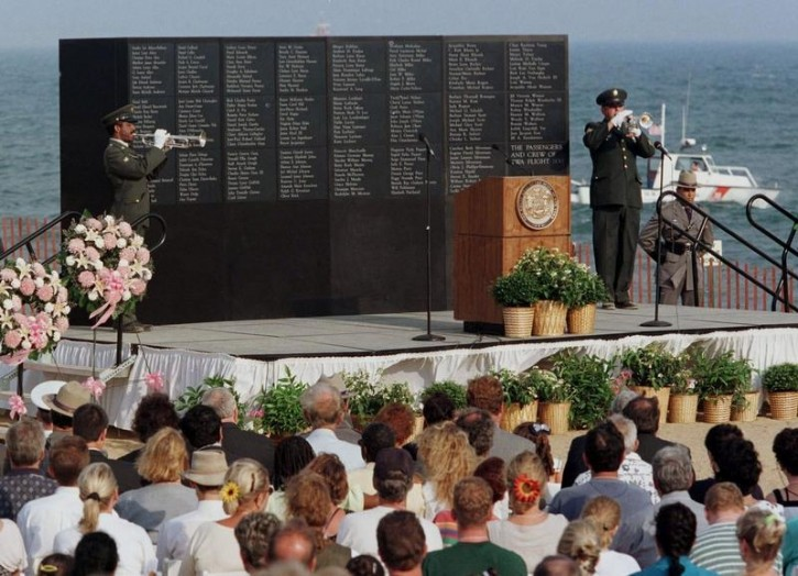 FILE - Family members and friends of victims of the crash of TWA flight 800 gather as taps is played on the one year anniversary of the disaster during a memorial service at Smith Point Park on July 17, 1996. Reuters