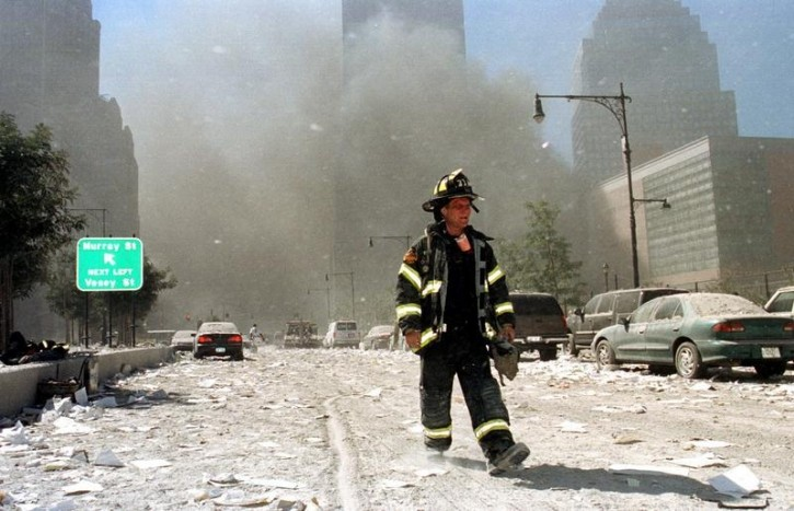 A New York City firefighter returns from battling building blazes near Vessey and Greenwich Streets after the World Trade Center collapse September 11, 2001. Reuters