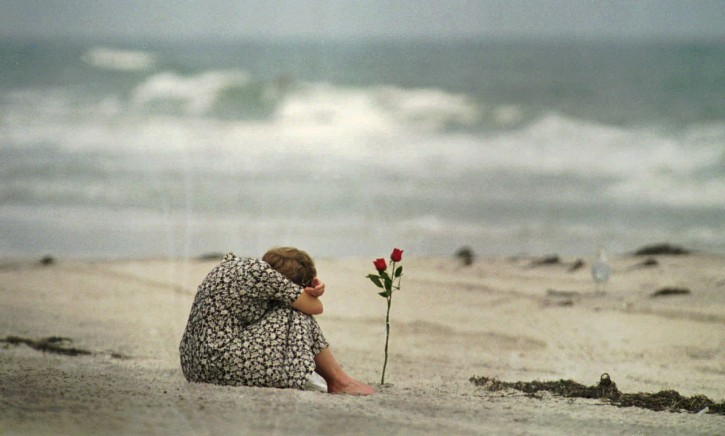 FILE - In this July 26, 1996, file photo, a woman sits near a rose she placed in the sand at Smith Point Park Beach in Shirley, N.Y. , as she mourns the loss of some of her friends who were on the flight crew for TWA Flight 800. Twenty years after the Boeing 747 exploded in a fireball off Long Island, killing all 230 aboard, the passage of time has been a salve for some, but others will never get over the heartache. (AP Photo/Mark Lennihan, File)