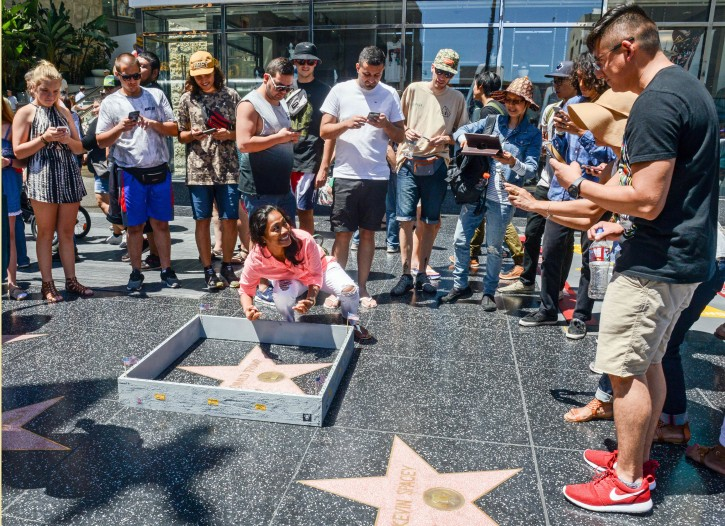 "This Tuesday, July 19, 2016 photo provided by Nick Stern shows a six-inch high, concrete-appearing 'wall,' created by an artist, surrounding the Hollywood Walk of Fame star of Donald Trump in Los Angeles. It appeared the day the former reality TV star and entrepreneur secured the Republican nomination for president. Tourists snapped photos of the wall, topped with razor wire and plastered with ""keep out"" signs. The tiny wall was gone by Wednesday morning. (Nick Stern via AP)"