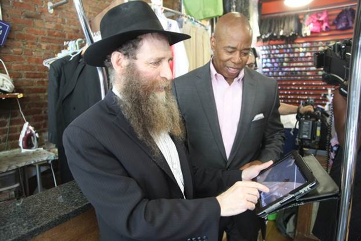 Brooklyn Borough President Eric L. Adams watches surveillance footage with Rabbi Eli Cohen, executive director of the Crown Heights Jewish Community Council, from a camera installed outside Mr Clean It, a dry cleaning business in Crown Heights, as part of Operation Safe Shopper, a partnership he established between local civic organizations and the NYPD to deploy security technology in commercial corridors across Brooklyn. Photo Credit: Patrick Rheaume/Brooklyn BP's Office<br />
