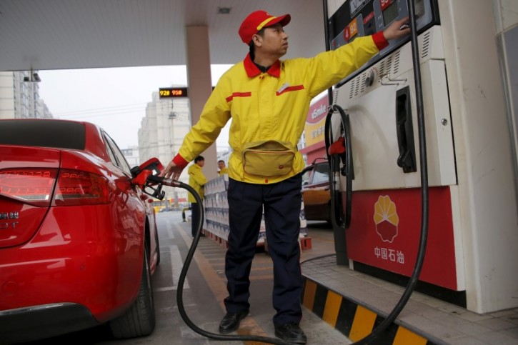 FILE - A gas station attendant pumps fuel into a customer's car at PetroChina's petrol station in Beijing, China, March 21, 2016. REUTERS/Kim Kyung-Hoon
