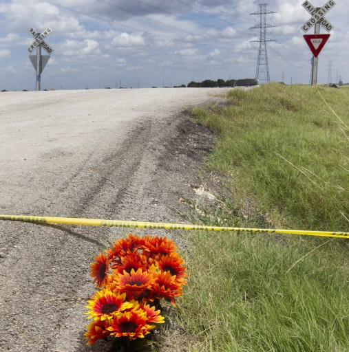 Flowers sit next to police tape at the site of Saturday's hot air balloon crash near Lockhart, Texas, Sunday, July 31, 2016. A hot air balloon made contact with high-tension power lines before crashing into a pasture in Central Texas, killing all on board, according to federal authorities who are investigating the worst such disaster in U.S. history. (Jessalyn Tamez/Austin American-Statesman via AP)