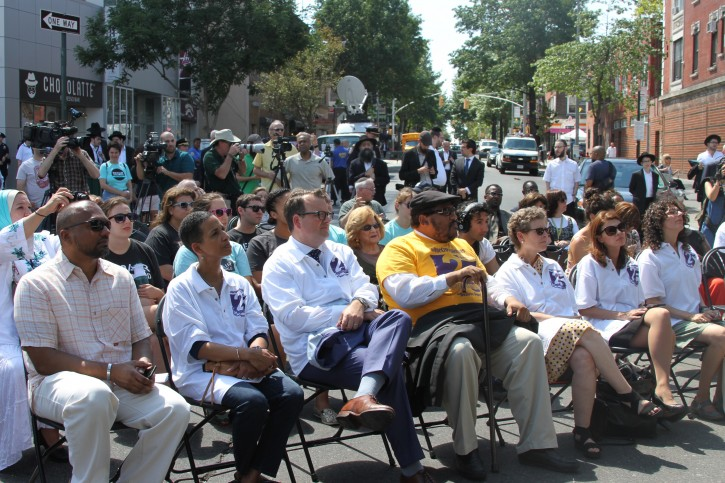 Members of the community attend service memorial service on Eastern Parkway in the Crown Heights neighborhood of the Brooklyn borough of New York on Sunday, Aug. 21, 2016 to mark the 25th anniversary of the riot that forever linked the Brooklyn neighborhood with images of racial unrest. In August 1991, a riot broke out in the Brooklyn area after 7-year-old Gavin Cato was struck and killed by a car in a rabbi's motorcade. Hours later, a Jewish doctoral student, Yankel Rosenbaum, was stabbed to death. Four days of violence followed. (AP Photo/Mike Balsamo)