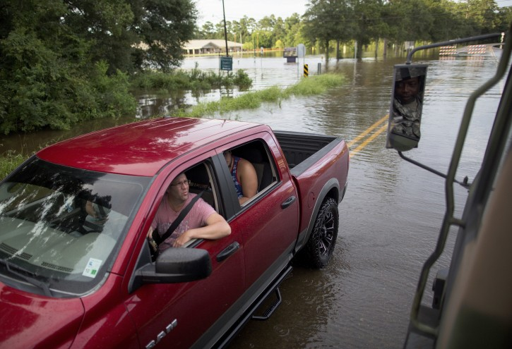 Army National Guard soldiers check on people fleeing the area around Hammond Eastside Elementary Magnet School in Hammond, La., after heavy rains inundated the region Saturday, Aug. 13, 2016. (AP Photo/Max Becherer)
