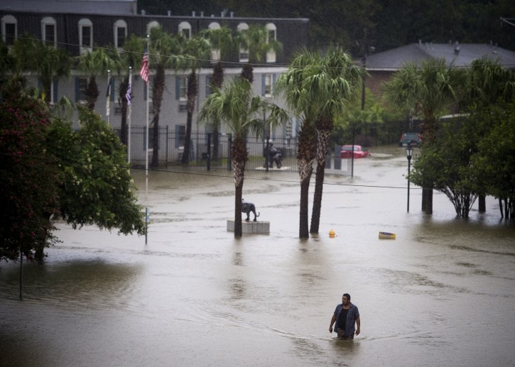 A resident wades through flood water at Tiger Manor Apartments by the North Gates of LSU, Saturday, Aug. 13, 2016, in Baton Rouge, La. Louisiana Gov. John Bel Edwards says more than 1,000 people in south Louisiana have been rescued from homes, vehicles and even clinging to trees as a slow-moving storm hammers the state with flooding. (Brianna Paciorka/The Advocate via AP)