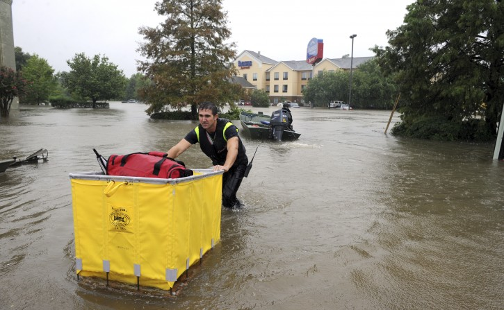 A Lafayette firefighter brings guests luggage to the street while evacuating them from the Fairfield Inn in Lafayette, La., Saturday, Aug. 13, 2016. Louisiana Gov. John Bel Edwards says more than 1,000 people in south Louisiana have been rescued from homes, vehicles and even clinging to trees as a slow-moving storm hammers the state with flooding. (Brad Kemp/The Advocate via AP)