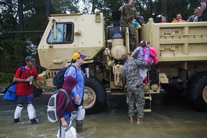 Kevin Richmond, left, and Barbara Manuel and her two children Elliott, age 8, and, center, and Emily, age 5, right, are rescued by members of the Louisiana Army National Guard from rising flood water near Walker, La., after heavy rains inundating the region, Sunday, Aug. 14, 2016. (AP Photo/Max Becherer)