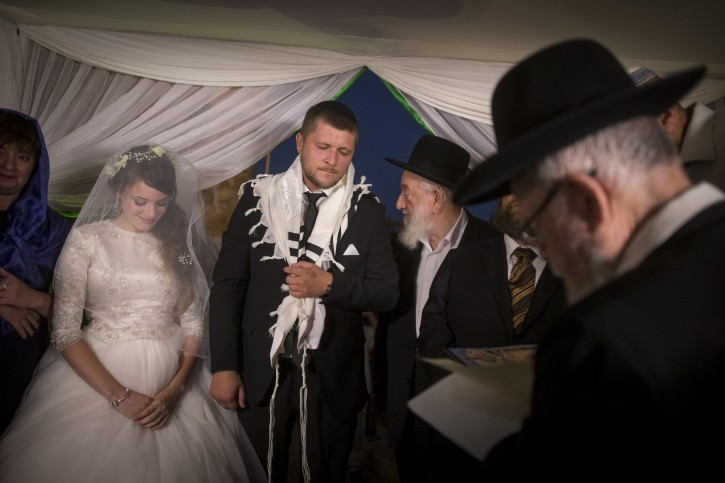 Meir Pawlowski and Katia, surrounded by their family, during their wedding ceremony in the Old City of Jerusalem, August 17, 2016, Meir Pawlowski was critically injured in a stabbing attack in Kiryat Arba a year ago. Photo by Yonatan Sindel/Flash90