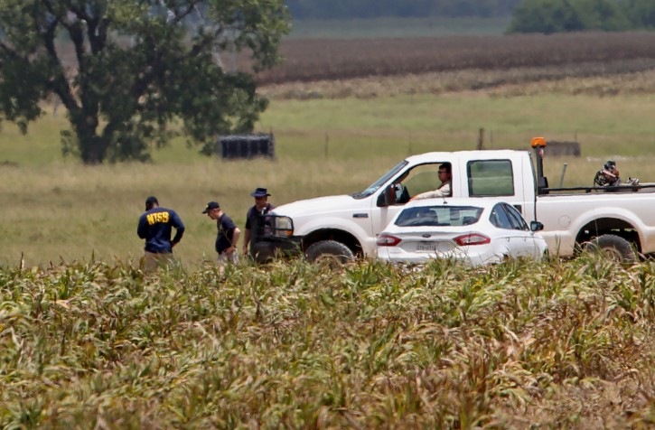 Investigators work the scene of Saturday's hot air balloon crash near Maxwell, Texas, Sunday, July 31, 2016. A hot air balloon made contact with high-tension power lines before crashing into a pasture in Central Texas, killing all on board, according to federal authorities who are investigating the worst such disaster in U.S. history. (Edward A. Ornelas/The San Antonio Express-News via AP)