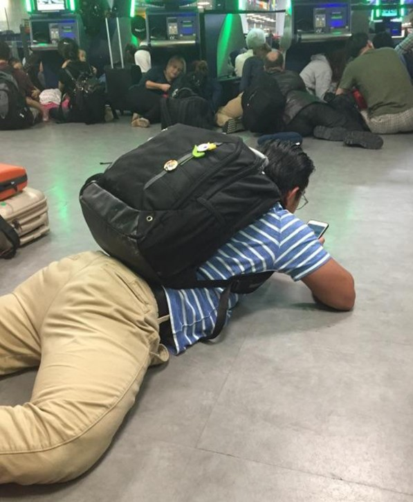 In this Aug. 14, 2016 photo provided by Diana Brooks, arriving passengers in the passport control area of New York's Kennedy Airport stay close to the ground after authorities ordered them to get down on the floor in fear of a possible shooter on the loose. Authorities said that sounds at first suspected to be gunshots, are still under investigation and that no one was hurt. Brooks, a resident of New York, was returning to JFK from Copenhagen. (Diana Brooks via AP)