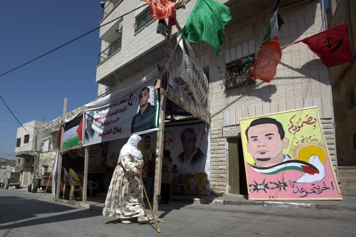 "In this Saturday, Aug. 13, 2016 photo, Palestinian woman walks in front of a tent set up in solidarity with Bilal Kayed, 34, in front of his family home in the village of Assira al-Shamaliya near the West Bank city of Nablus. Kayed, 34, started a hunger strike on June 14, after Israel ordered him held for six months without charges, immediately following his completion of a 14-and-a-half-year prison term for shooting at Israeli troops. Poster on the left reads: ""We will be the spearhead in the confrontation."" Poster on the right says: ""Your steadfastness will defeat the wardens. Freedom is our destiny."" (AP Photo/Majdi Mohammed)"