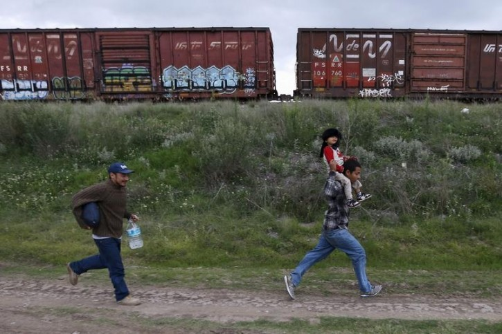FILE - A Salvadoran father (R) carries his son while running next to another immigrant as they try to board a train heading to the Mexican-U.S. border, in Huehuetoca, near of Mexico City, June 1, 2015.  AP