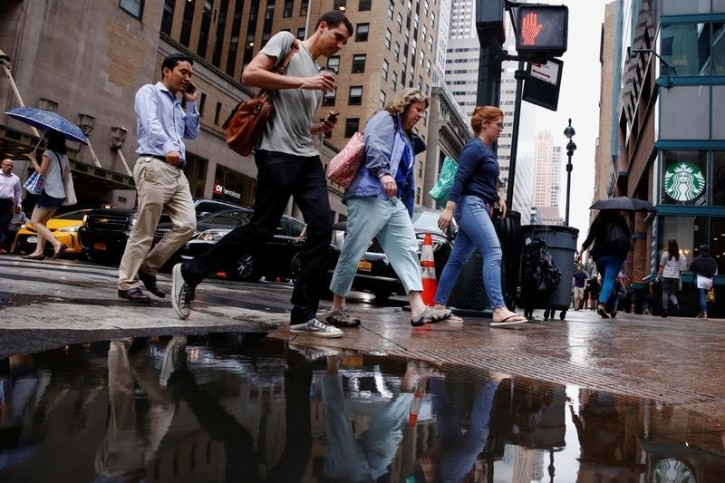 Pedestrians avoid a water puddle after a summer rain in New York, U.S., August 10, 2016.  REUTERS/Lucas Jackson