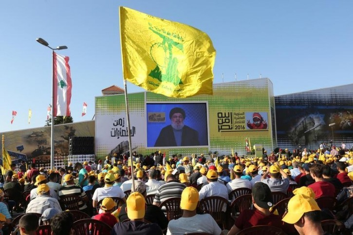 Supporters of Lebanon's Hezbollah leader Sayyed Hassan Nasrallah display Hezbollah and Lebanese flags as they listen to him via a screen during a rally marking the 10th anniversary of the end of Hezbollah's 2006 war with Israel, in Bint Jbeil, southern Lebanon August 13, 2016. REUTERS/Aziz Taher