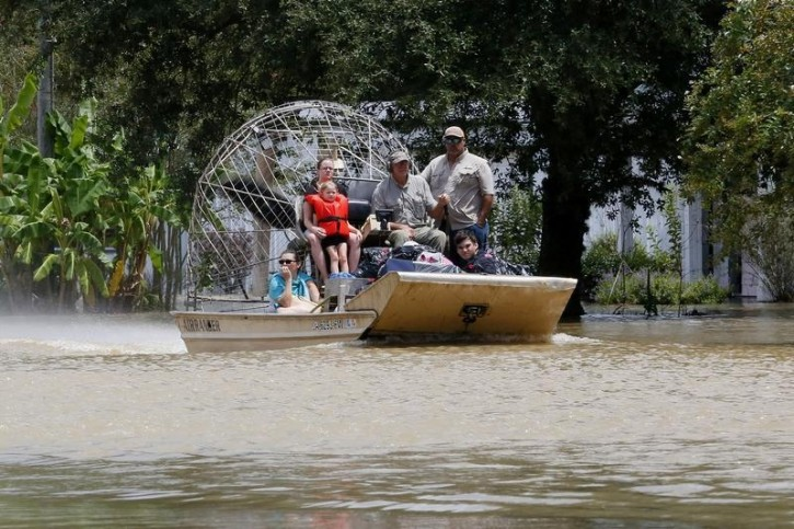 An airboat brings rescued residents to safety in Ascension Parish, Louisiana, U.S., August 15, 2016.  REUTERS/Jonathan Bachman