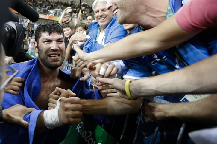 Israel's Or Sasson celebrates with supporters after winning the bronze medal during the men's over 100-kg judo competition at the 2016 Summer Olympics in Rio de Janeiro, Brazil, Friday, Aug. 12, 2016. (AP Photo/Markus Schreiber)