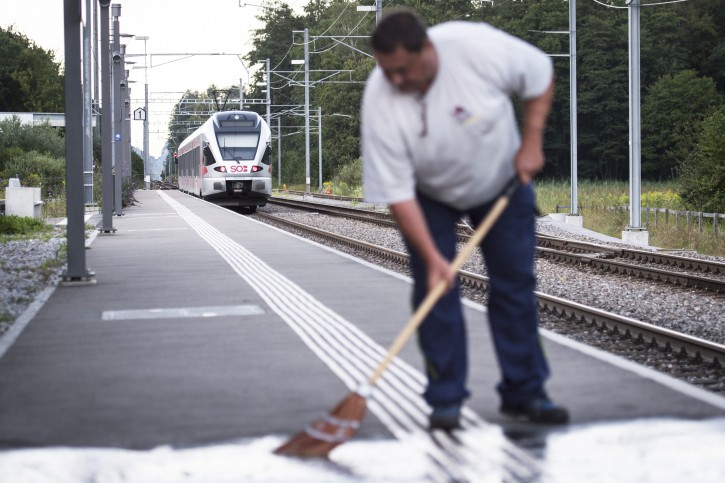 In this Aug. 13, 2016 picture a man cleans the platform as the train stands at the station following an attack onboard, in Salez, Switzerland.  AP