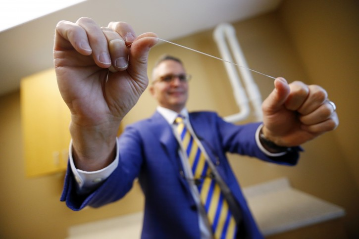 Dr. Wayne Aldredge, president of the American Academy of Periodontology, holds a piece of dental floss at his office in Holmdel, N.J. Aldredge acknowledges the weak scientific evidence and the brief duration of many studies on flossing, but says that the impact of floss might be clearer if researchers focused on patients at the highest risk of gum disease, such as diabetics and smokers. (AP Photo/Julio Cortez)