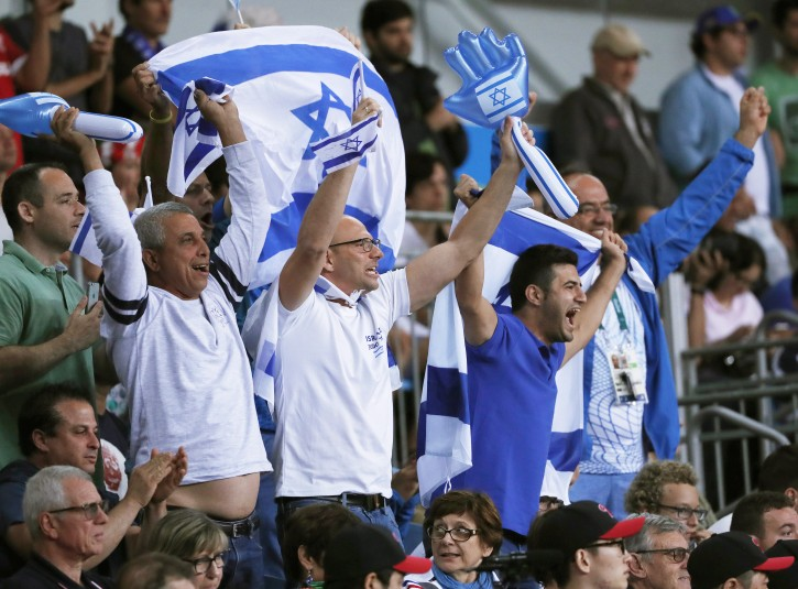 Fans fly the Israeli flag as they cheer on Or Sasson of Israel facing Roy Meyer of the Netherlands in the men's +100kg quarter final bout of the Rio 2016 Olympic Games Judo events at the Carioca Arena 2 in the Olympic Park in Rio de Janeiro, Brazil, 12 August 2016.  EPA/ORLANDO BARRIA