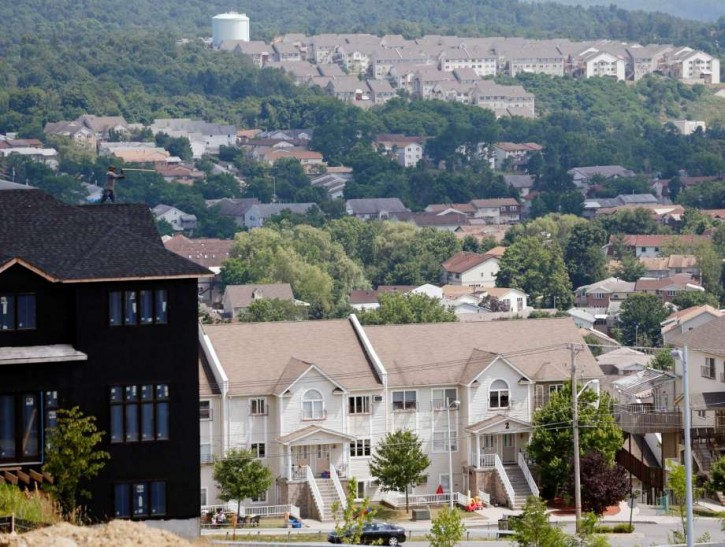 FILE - In this July 1, 2014, file photo, a new housing unit, left, is under construction in Kiryas Joel, N.Y. (AP Photo/Mike Groll, File)