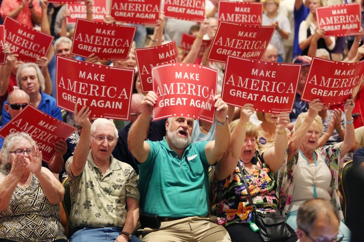Supporters cheer and wave signs as Republican vice presidential candidate Mike Pence speaks at a campaign rally at The Villages, Fla., on Saturday, Sept. 17, 2016. (Stephen M. Dowell/Orlando Sentinel via AP)