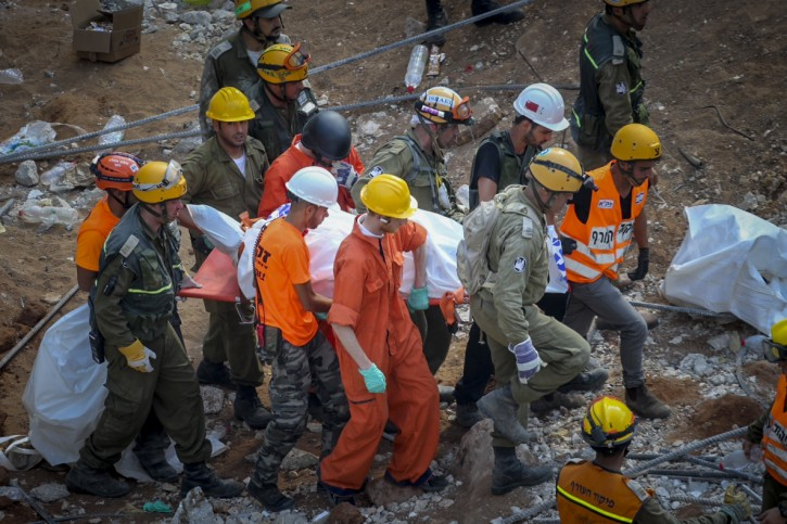 FILE - Rescue workers evacuate a dead person from the site of a building collpase at a construction site on September 06, 2016, in the Ramat Hahayal neighborhood of Tel Aviv. Flash90