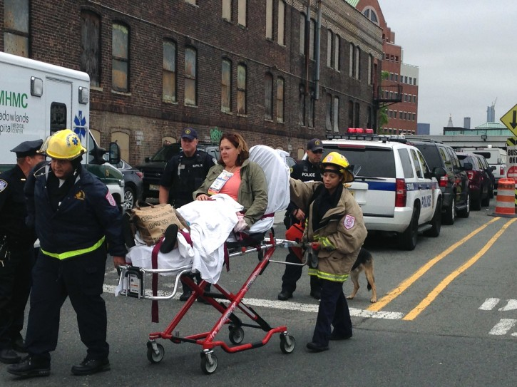 A woman is wheeled away from the Hoboken Terminal train station on a stretcher Thursday Sept. 29, 2016, after a New Jersey Transit commuter train from New York barreled into the station during the morning rush hour, in Hoboken, N.J. The crash caused an unknown number of injuries and witnesses reported seeing one woman trapped under concrete and many people bleeding. (AP Photo/Karen Matthews)