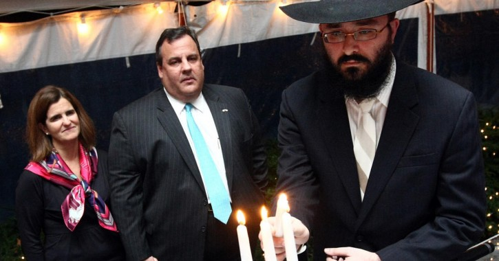 FILE - Governor Chris Christie and First Lady Mary Pat Christie look on while  Rabbi Mendy Carlebach lights the Menorah during the Hanukkah Holiday Reception at Drumthwacket in Princeton, N.J. on Monday, Dec. 10, 2012. (Governor's Office/Tim Larsen)