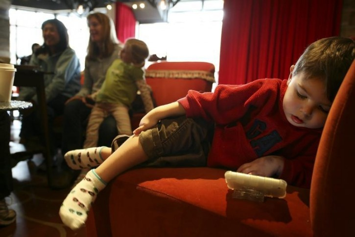 FILE - A boy watches a video on his Mom's iPhone while she talks with friends at Starbucks' Roy Street Coffee and Tea in Seattle, Washington, March 25, 2010. REUTERS/Marcus Donne
