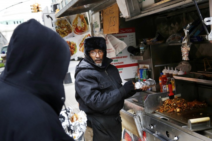Mohammeed Shaheedul Huq serves a customer from his food cart in the Brooklyn  borough of New York, Monday, Nov. 21, 2016. The strict limits on street cart licenses that's been in place for decades has led to a throng of illegal carts and a black market where leasing a $300 license can run up to $20,000. Legislation to raise the cap is under consideration, but opponents say more carts would only further clog city streets and cause harm to bricks and mortar restaurants and businesses.  (AP Photo/Seth Wenig)