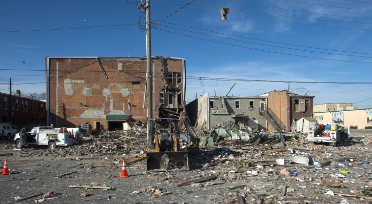 Debris is scattered at the site of a natural gas explosion Thursday, Nov. 17, 2016 in Canton Ill. Authorities on Thursday were investigating the cause of a Wednesday evening gas explosion that rocked downtown homes and businesses in a central Illinois community, shattering glass and cracking interior walls in nearby buildings. (David Zalaznik/Journal Star via AP)