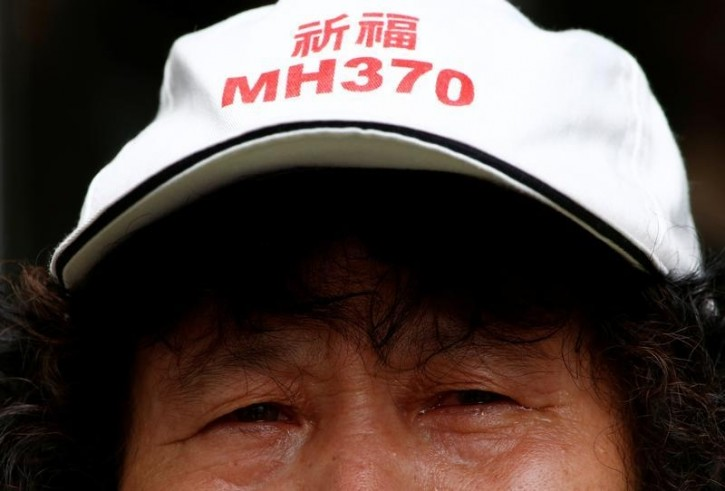 """FILE - A family member of a passenger aboard Malaysia Airlines flight MH370 which went missing in 2014 reacts during a protest outside the Chinese foreign ministry in Beijing, July 29, 2016. The hat reads """"Pray for MH370"""" REUTERS/Thomas Peter"""