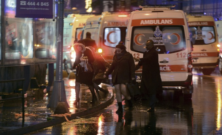 People leave as medics and security officials work at the scene after an attack at a popular nightclub in Istanbul, early Sunday, Jan. 1, 2017. AP