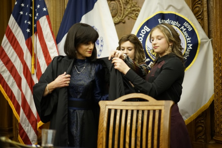 The three daughters of Ruchie, Shaindy Fink, Leah Freier and Faigy Freier, put the Judicial robe on their mom.