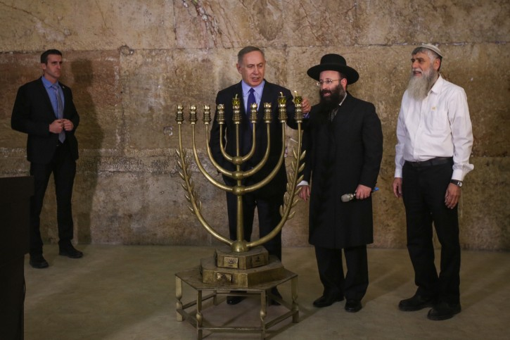 Israeli Prime Minister Benjamin Netanyahu lights the 'Chanuckia' on the First night of the Jewish holiday of Hanukkah at the Western Wall in Jerusalem Old City on December 25, 2016. Photo by Marc Israel Sellem/POOL