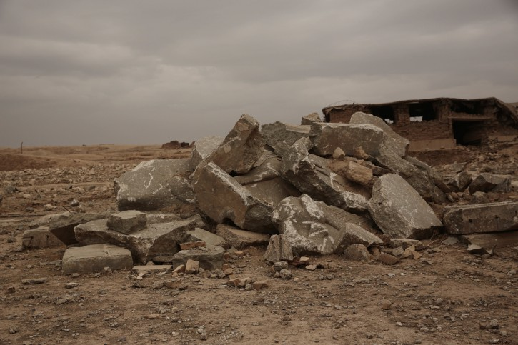 The remains of a large stone figure of a lamassu, an Assyrian winged bull deity, are piled near the gates of the ancient palace where they once stood at Nimrud, Iraq  in this Wednesday, Dec. 14, 2016 photo. Islamic State group extremists detonated explosives throughout the palace, destroying its elaborate reliefs showing gods, mythical beasts and kings, and reducing it t a field of rubble. (AP Photo/Maya Alleruzzo)